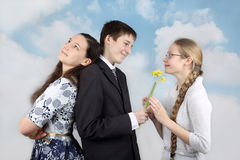 Boy gives flowers to girlfriend. Teenage boy stands back to back with one girl and gives flowers to another on cloudy blue sky background - Inconstancy and Stock Images