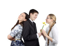 Boy gives flowers to girlfriend. Teenage boy stands back to back with one girl and gives flowers to another isolated on white background - Inconstancy and Royalty Free Stock Photos