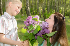 The boy gives flowers to his mother. The boy gives flowers to his mother royalty free stock photo