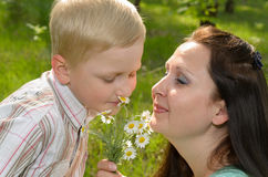 The boy gives flowers to his mother.  stock image