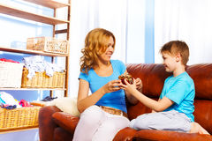 Boy gives gift to his mother on brown sofa. Boy presents a gift to his mother while looking at her on brown leather sofa at home stock photography