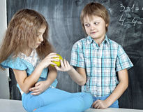 Boy gives a girl an apple at school Stock Photography