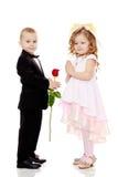 The boy gives the girl a flower. Stock Photos