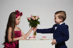 Boy gives a girl flowers.little beautiful couple Royalty Free Stock Photography