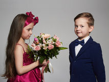 Boy gives a girl flowers.little beautiful couple Royalty Free Stock Image