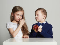 Boy gives a girl gift.little beautiful couple.kids Royalty Free Stock Photos