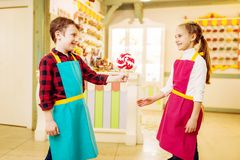 Boy gives handmade lollipop to his girlfriend. Little boy gives handmade lollipop to his smiling girlfriend. Children in workshop at pastry shop. Holiday fun in Stock Image