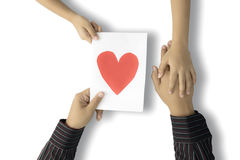 Boy gives a heart symbol to father. Top view of a boy giving a heart symbol on the paper to his father, isolated on white background Stock Photography