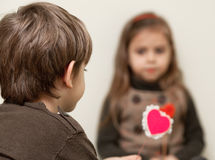 Boy gives heart to little girl. Little girl and boy with red heart Stock Images