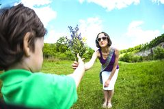 The boy gives his mother a bouquet. The boy gives his mother a bouquet of wild flowers. A women is walking with her son in a meadow. A gift for mother`s day royalty free stock photography