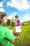 The boy gives his mother a bouquet. The boy gives his mother a bouquet of wild flowers. A women is walking with her son in a meadow. A gift for mother`s day royalty free stock image