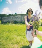 The boy gives his mother a bouquet. The boy gives his mother a bouquet of wild flowers. A women is walking with her son in a meadow. A gift for mother`s day stock photography