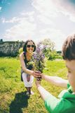 The boy gives his mother a bouquet. The boy gives his mother a bouquet of wild flowers. A women is walking with her son in a meadow. A gift for mother`s day royalty free stock photo