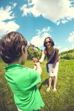 The boy gives his mother a bouquet. The boy gives his mother a bouquet of wild flowers. A women is walking with her son in a meadow. A gift for mother`s day stock images