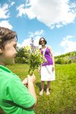 The boy gives his mother a bouquet. The boy gives his mother a bouquet of wild flowers. A women is walking with her son in a meadow. A gift for mother`s day stock photos
