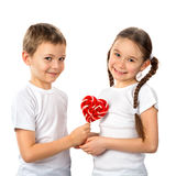 Boy gives a little girl candy lollipop heart isolated on white. Valentine`s day. Kids love. Stock Image