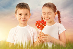 Boy gives a little girl candy red lollipop in heart shape on sunset field. Valentine`s day. Kids love. Stock Photos