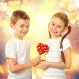 Boy gives a little girl candy red lollipop in heart shape. Valentine`s day art portrait. Royalty Free Stock Images
