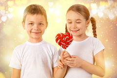 Boy gives a little girl candy red lollipop in heart shape. Valentine`s day. Kids love. Royalty Free Stock Image