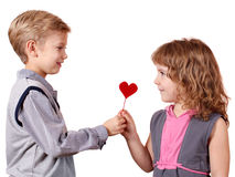 Boy gives a little girl heart. Boy gives a little girl red heart Royalty Free Stock Photos