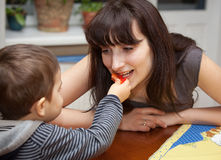 Boy gives a piece of red pepper to mother Royalty Free Stock Images