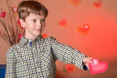 Boy gives a pink heart on Valentines Day. Stock Image