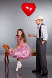 The boy gives a red balloon to the girl Stock Photos