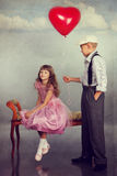 The boy gives a red balloon to the girl Royalty Free Stock Photos