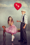 The boy gives a red balloon to the girl Stock Images