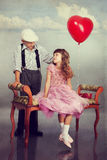 The boy gives a red balloon to the girl Royalty Free Stock Image