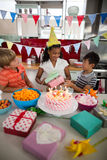 Boy giving birthday present to his sister in kitchen. At home stock photos