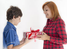Boy is giving christmas gift to his mother Stock Image