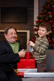 Boy giving christmas present to grandfather Royalty Free Stock Photo