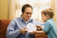 Boy giving dad drawing. Stock Photos