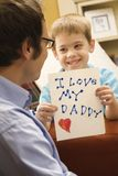 Boy giving dad drawing. Stock Images
