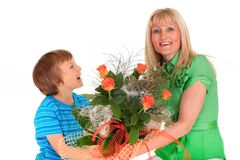 Boy giving flowers to mom. Studio horizontal portrait of a smiling young boy giving his happy mother a bouquet of peach flowers.  Isolated on a white background Royalty Free Stock Image