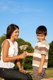 Boy giving flowers to mum. Child holding out bunch of flowers to  his mother Royalty Free Stock Photo