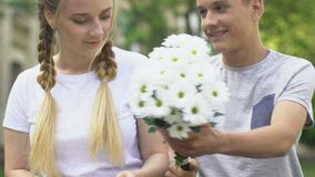 Boy giving flowers to pretty girl, pleasant surprise, first love in adolescence. Stock footage stock video footage