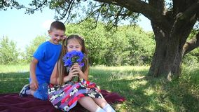 Boy is giving flowers to pretty girl. young couple in love. two adorable children in sunny park. happy people over green. Nature background stock video