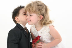 Boy Giving Girl A Kiss. Toddler boy giving pretty 4 year old girl a kiss on the cheek. Shot in studio over white Stock Photos