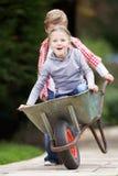 Boy Giving Girl Ride In Wheelbarrow Stock Photos