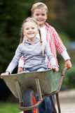 Boy Giving Girl Ride In Wheelbarrow Royalty Free Stock Images