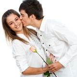 Boy giving girl a rose and romantic kiss. Royalty Free Stock Photography