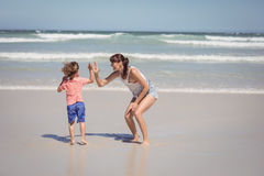 Boy giving high five to mother on shore Stock Image