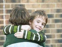 Boy Giving a Hug. Boy Smiling Giving Brother a Big Hug Royalty Free Stock Images