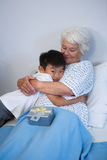 Boy giving a hug to senior patient on bed. At hospital Royalty Free Stock Photography