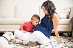 Boy Giving A Kiss On Pregnant Mother`s Abdomen At Home. Cute boy giving a kiss on pregnant mother`s abdomen at home Royalty Free Stock Photography