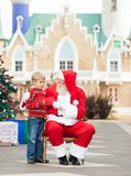 Boy Giving Letter To Santa Claus Royalty Free Stock Images