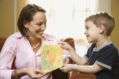 Boy giving mom a drawing. stock photo