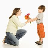 Boy giving mother flowers. Son giving bouquet of flowers to mother Stock Photography